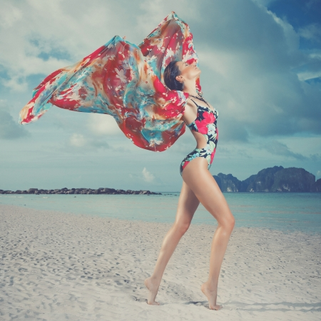 beach butterfly: Luxurious woman in color dress on the beach
