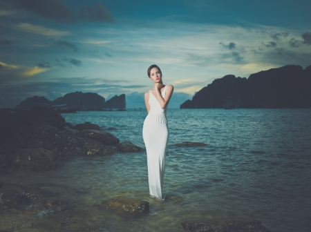 Beautiful lady in a white dress on a rocky shore