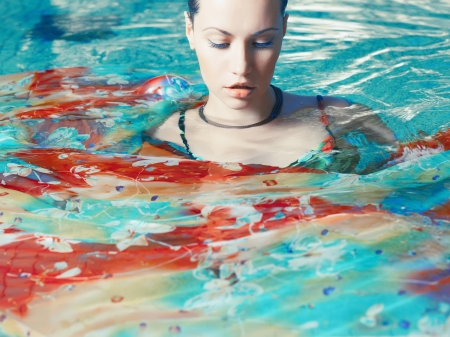 wet dress: Photo of beautiful woman in a bright dress in the pool Stock Photo