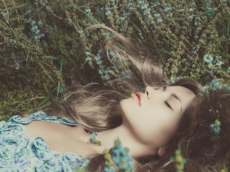美しい官能的な女性の花の草原に横たわっています。 写真素材