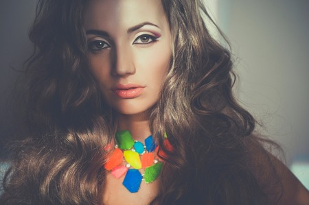 stares: Portrait of beautiful young woman with bright necklace