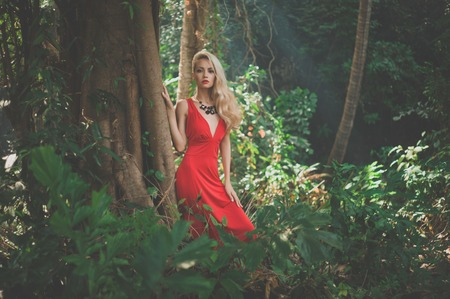 Young beautiful lady in red dress in tropical forest