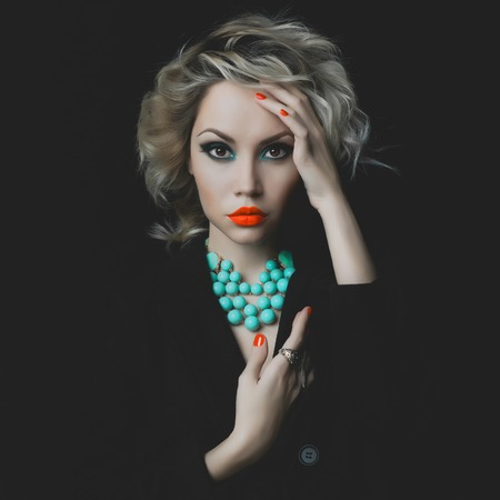 Fashion photo of a beautiful blonde with bright makeup and jewelry photo