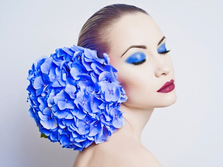 Fashion portrait of beautiful young lady with blue hydrangea Imagens