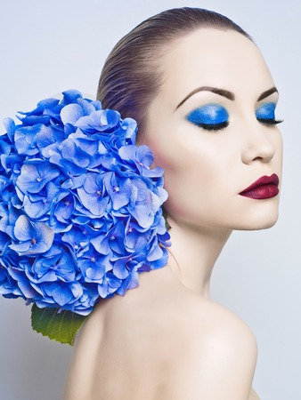 Fashion portrait of beautiful young lady with blue hydrangea photo