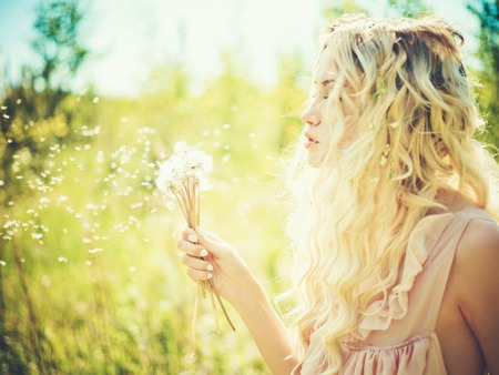 Outdoor fashion portrait of romantic blonde with dandelions