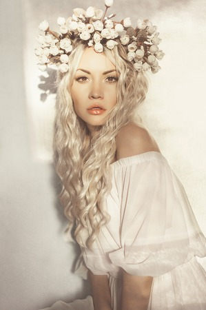 Fashion-art portrait of romantic blonde with wreath of flowers