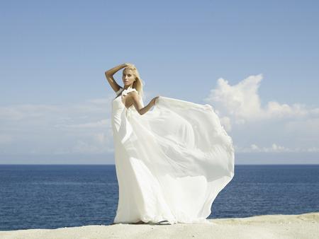 Fashion photo of beautiful elegant bride at the seashore