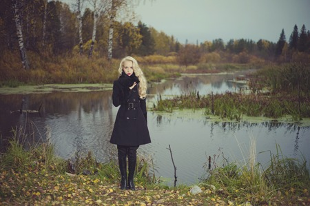 Beautiful elegant woman in a black coat on the river bank photo
