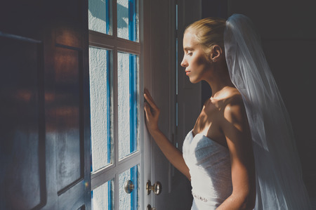 Art photo of beautiful bride waiting at the window Stock Photo