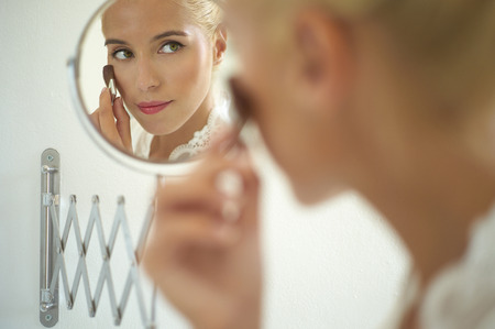 corrects: Beautiful bride in the mirror corrects make-up. Fashion art photo