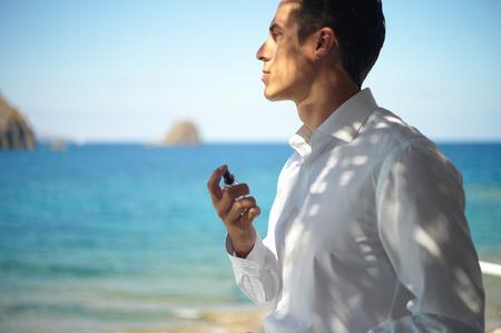 Knappe jonge man spuiten parfum. Mode foto Stockfoto