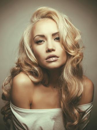 壮大なブロンドの髪と美しい女性の写真。髪の拡張子、パーマ