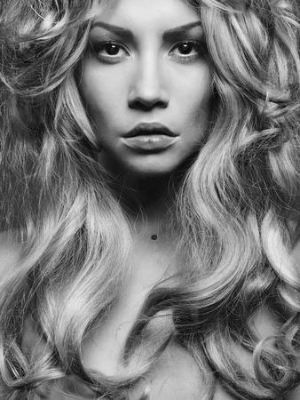 壮大なブロンドの髪と美しい女性の黒と白の肖像画。髪の拡張子、パーマ