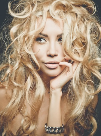 long curly hair: Beautiful woman with magnificent blond hair. Hair extension, permed Stock Photo