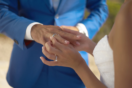 diamond rings: The bride wears a wedding ring on the groom. Closeup photo