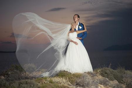 Fashion art photo of bride and groom on the seashore. Wedding photo