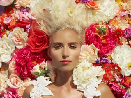 Mooie blonde jonge vrouw, liggend in de bloemen