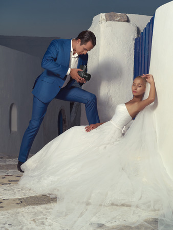 fashionable couple: Bride posing while her groom is shooting with an old camera Stock Photo