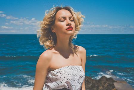 海で美しい金髪の若い女性の肖像画