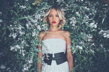 modelos posando: Retrato de la se�ora hermosa rom�ntica en el jard�n de flores