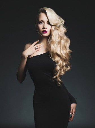 elegant dress: Fashion-art photo of elegant blonde on black background