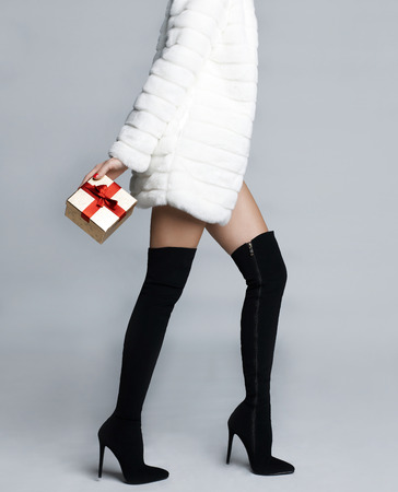 Slender female in elegant boots stockings with gift