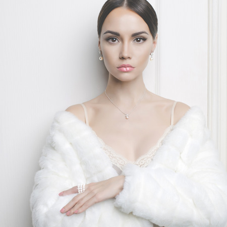 Fashion photo of beautiful lady in elegant white fur coat Imagens