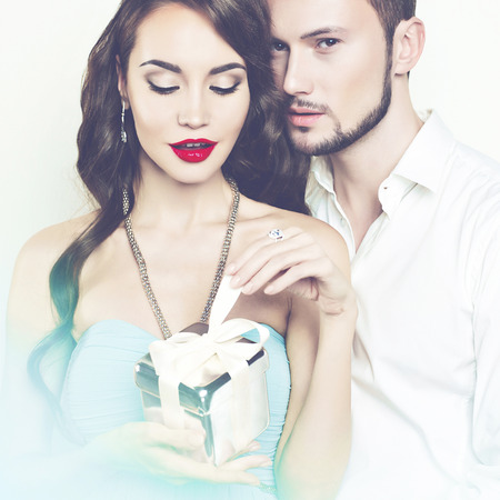 sexual couple: Fashion photo of beautiful romantic couple with gift