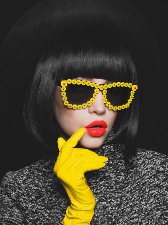 Fashion studio photo of stylish lady in gloves and sunglasses Standard-Bild