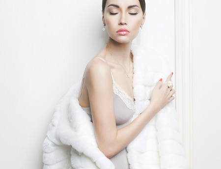 seducing: Fashion photo of beautiful lady in elegant white fur coat Stock Photo