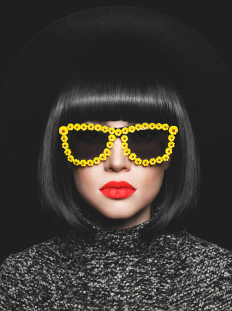 Fashion studio photo of stylish lady in hat and sunglasses Фото со стока