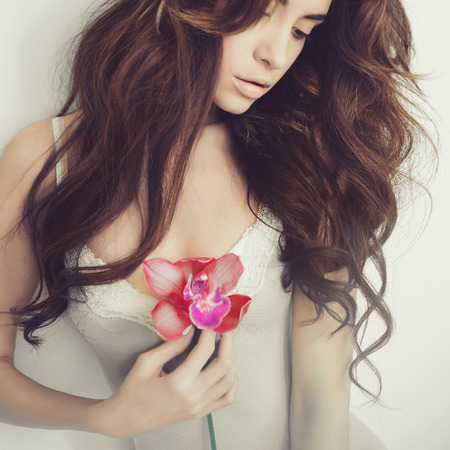 Fashion art portrait of beautiful lady with delicate flowers Stock Photo
