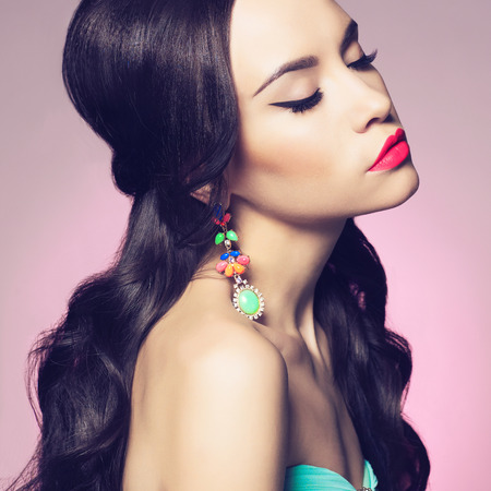 Fashion studio portrait of beautiful young woman with earring. Jewelry and accessories Фото со стока