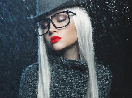 Beautiful woman looking through the window with rain drops