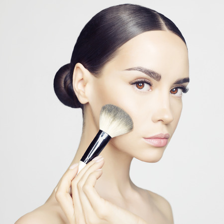 Studio fashion photo of beautiful young lady applying blush. Beauty and care. Extension eyelashes. Spa salon. Perfect face makeup Foto de archivo