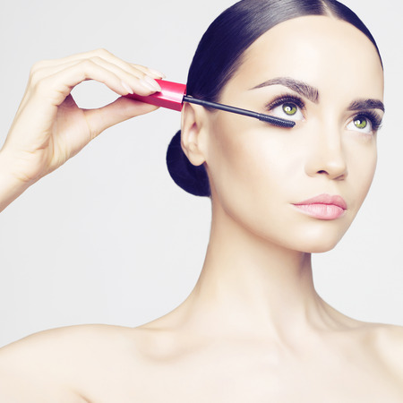mascara: Studio fashion photo of beautiful young lady applied mascara.  Beauty and care. Extension eyelashes. Spa salon. Perfect face makeup