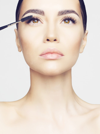 Studio fashion photo of beautiful young lady applied mascara.  Beauty and care. Extension eyelashes. Spa salon. Perfect face makeup
