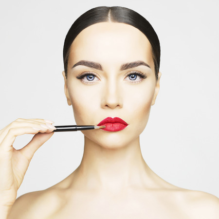 スタジオ ファッション写真の美しい若い女性は、口紅を適用されます。 完璧な顔メイク
