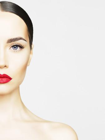 Lipstick: Studio chân dung của người phụ nữ trẻ xinh đẹp với làn da hoàn hảo. Làm đẹp và chăm sóc. tiệm Spa. Cây son đỏ