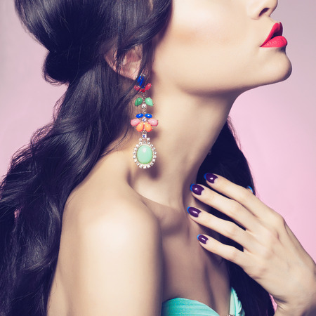 jewelry: Fashion studio portrait of beautiful young woman with earring. Beauty and manicure. Jewelry and accessories