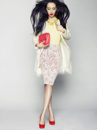 skirts: Beautiful brunette model in fashion clothes posing in studio. Wearing coat, handbag, red shoes