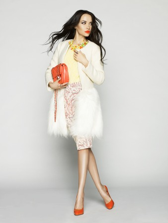 mode: Mooi donkerbruin model in de mode kleren poseren in de studio. Het dragen van jas, handtas, rode schoenen Stockfoto