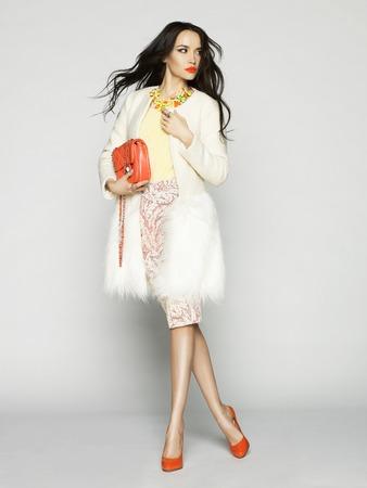fashion: Schöne Brünette Modell in modischer Kleidung im Studio aufwirft. Verschleißschicht, Handtasche, rote Schuhe