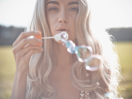 Outdoors fashion photo of beautiful blonde blowing bubbles