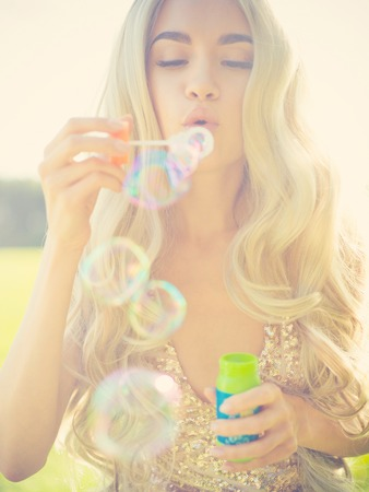blonde females: Outdoors fashion photo of beautiful blonde blowing bubbles