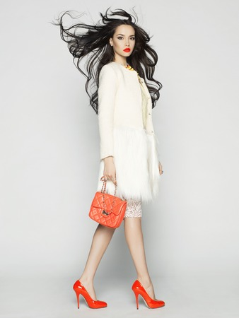 Beautiful brunette model in fashion clothes posing in studio. Wearing coat, handbag, red shoes