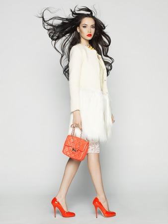 Schöne Brünette Modell in modischer Kleidung im Studio aufwirft. Verschleißschicht, Handtasche, rote Schuhe Standard-Bild - 42194237