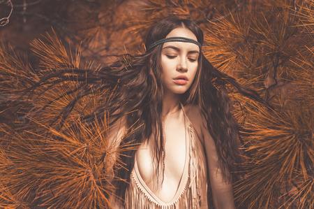 Outdoor mode foto van mooie dame hippie in een sparrenbos