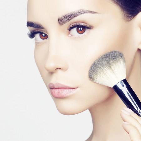 Studio fashion photo of beautiful young lady applying blush.